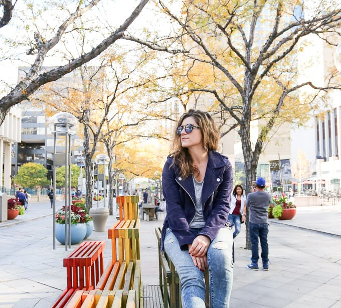 travel outfit: suede moto jacket, heeled gray boots, denim