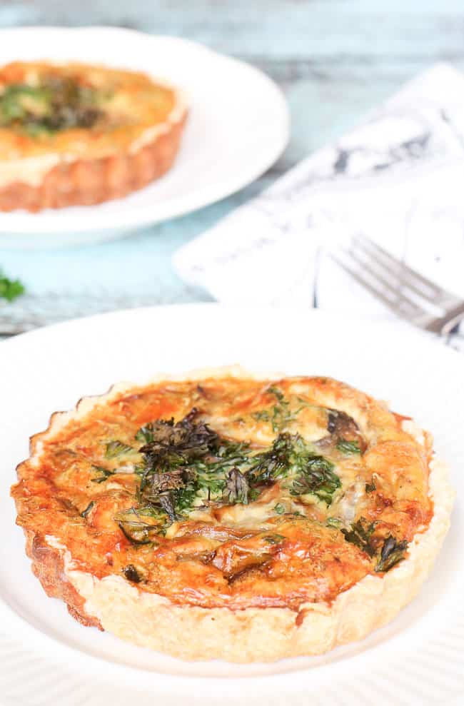 Mini rosemary onion quiche with garlic and mushrooms - so cheesy and delicious. Perfect for breakfast or dinner. Made in individual tart pans!