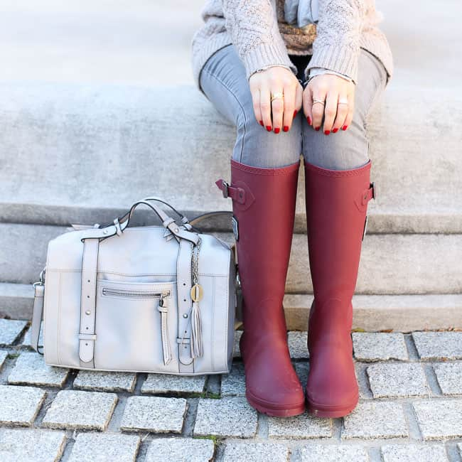 a neutral-themed outfit with a taupe sweater and scarf, light gray bag, and red rain boots