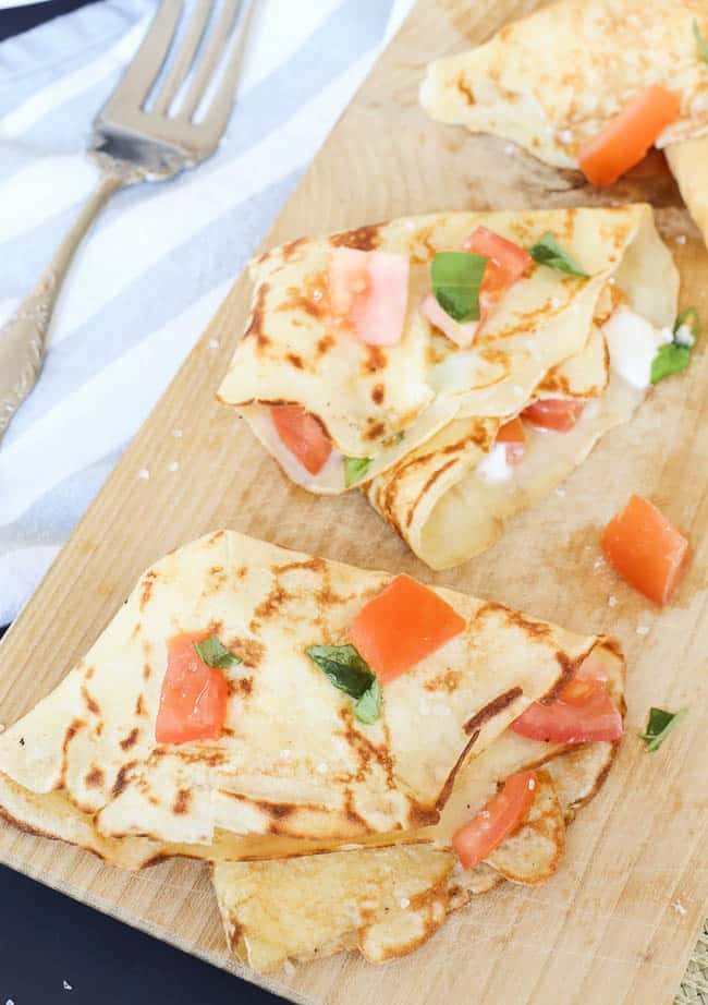 Savory crepes topped stuffed with melted burrata and topped with tomatoes and basil
