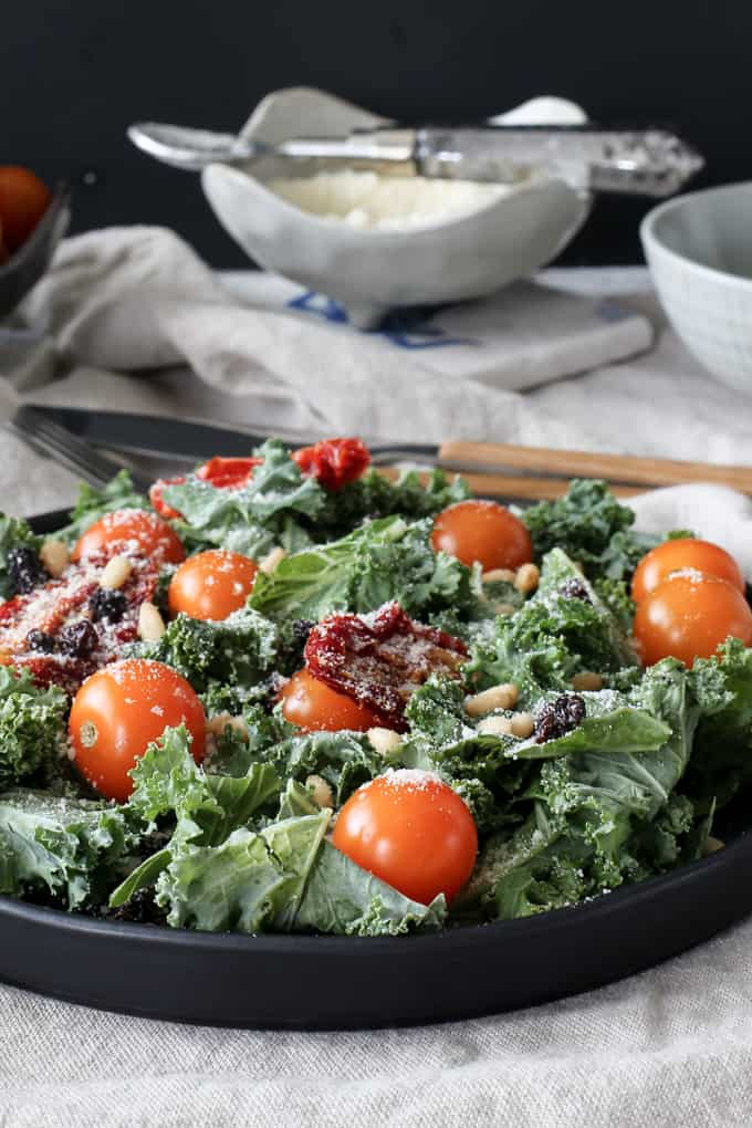 Healthy kale salad with sundried tomatoes, currants, tomatoes and pine nuts