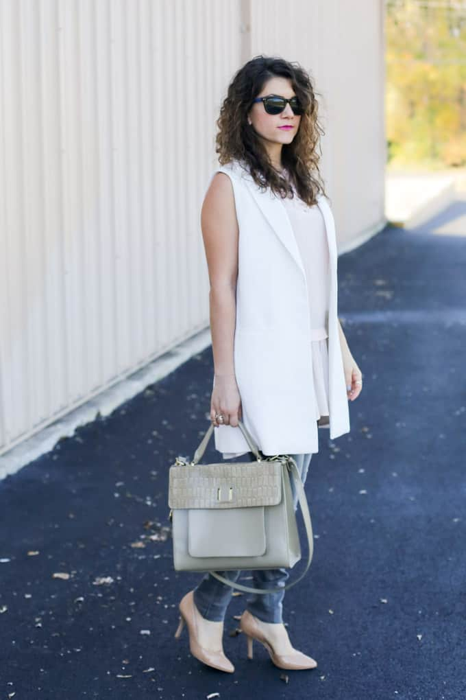 Gray denim with a cream vest and ruffled pink top , paired with neutral accessories