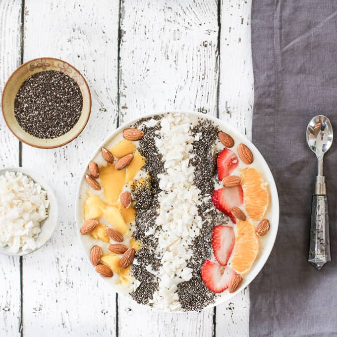 tropical smoothie bowl with coconut, chia seeds, almonds, mangoes and orange wedges
