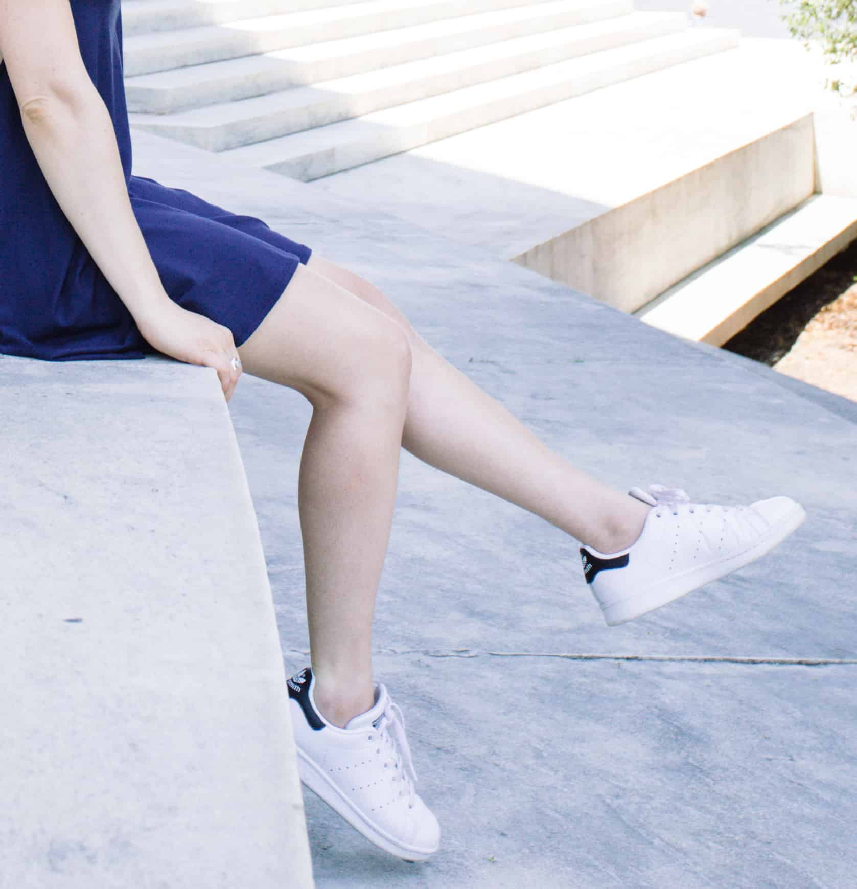 Summer casual outfit: navy dress and white Adidas sneakers