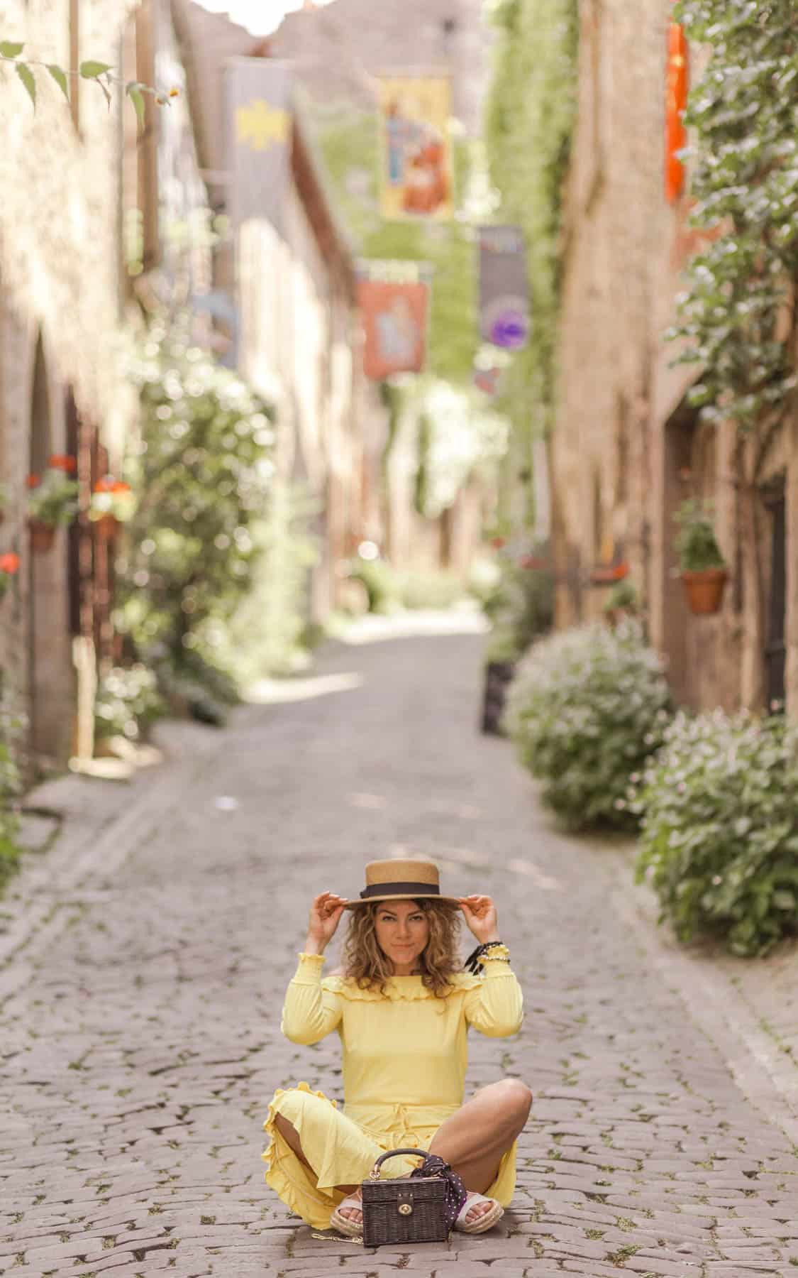 girl in boater hat and yellow dress sitting cross-legged in a medieval street