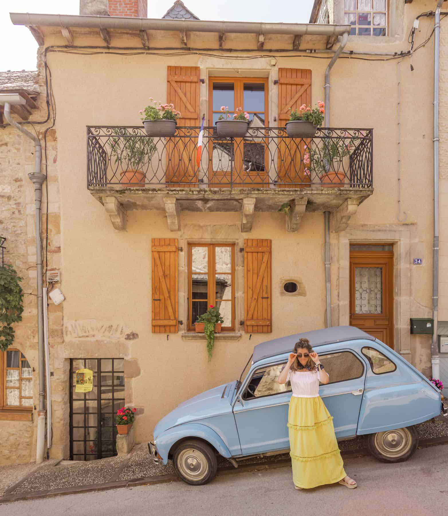 girl in yellow skirt posing in front of a vintage blue car and cute house in France