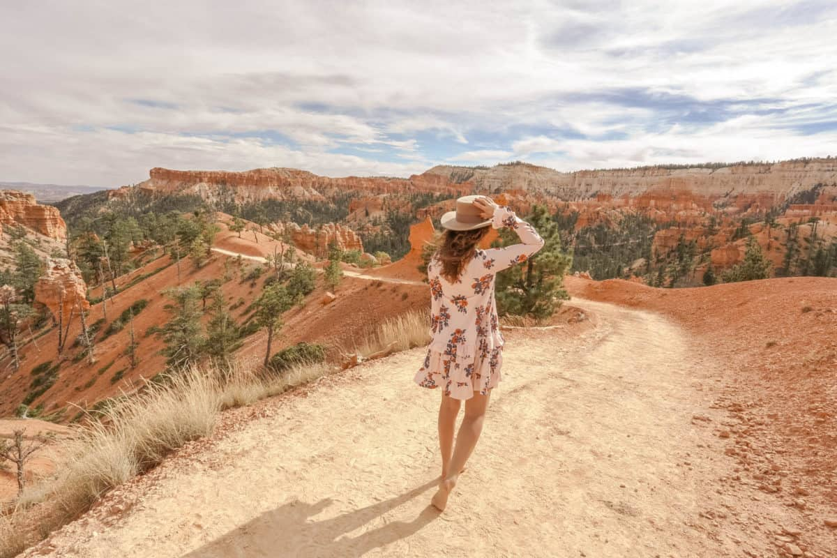 girl in long sleeve, short floral dress and hat walking barefoot on a dirt path in Bryce Canyon Utah