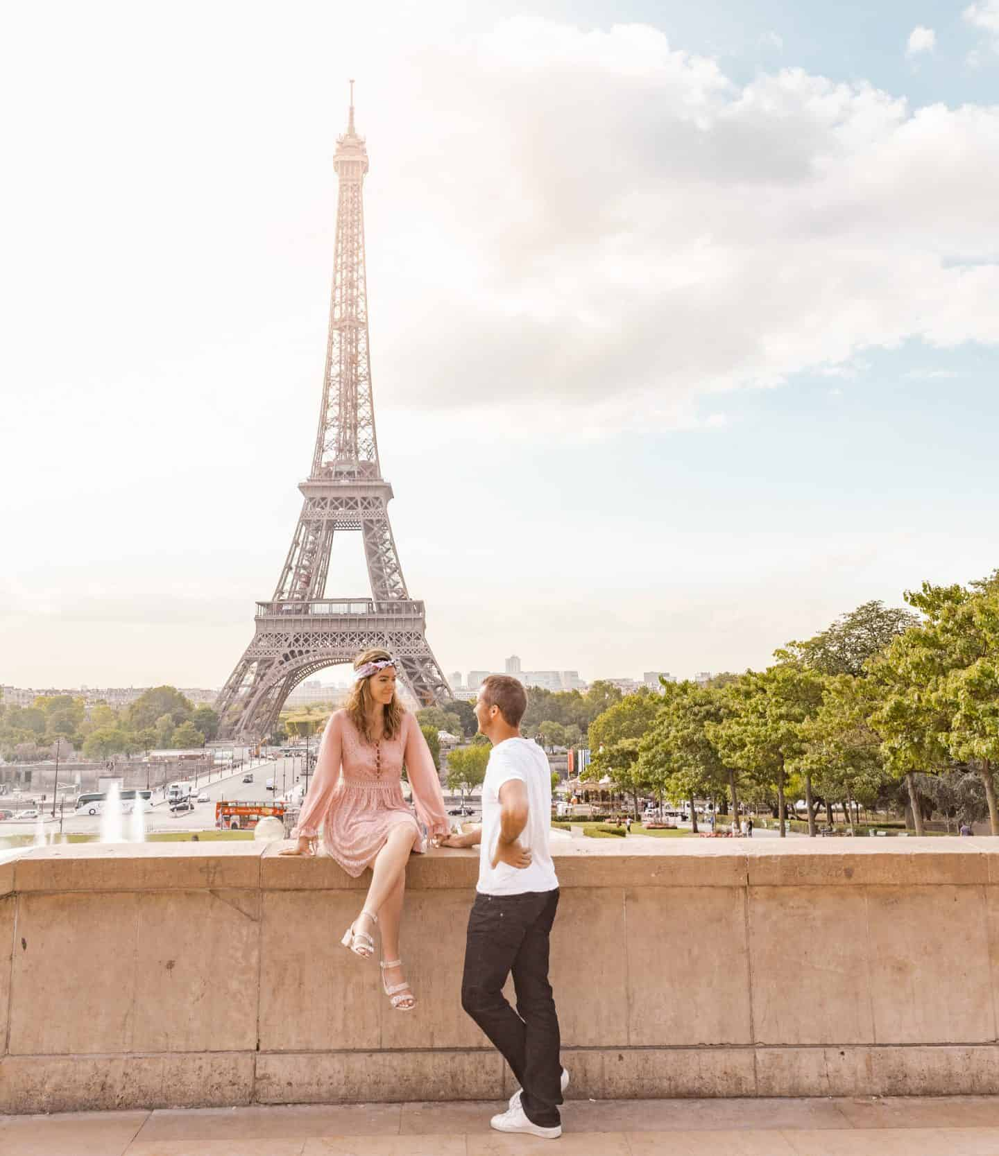woman in pink dress and man in black denim and white shirt posed together with Eiffel Tower in the background
