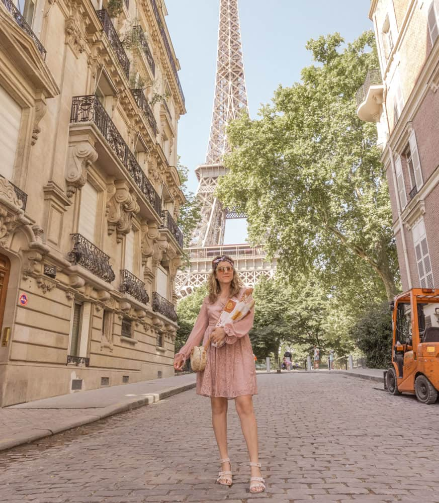 woman posed in front of the Eiffel Tower with a baguette in her arms