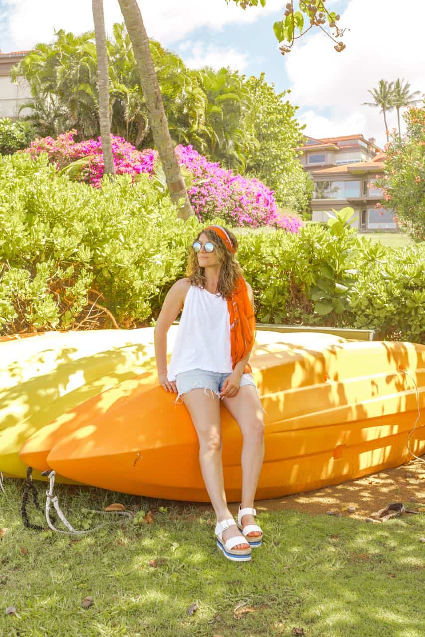 posed with yellow kayaks in the background and dressed in denim shorts and a white tank