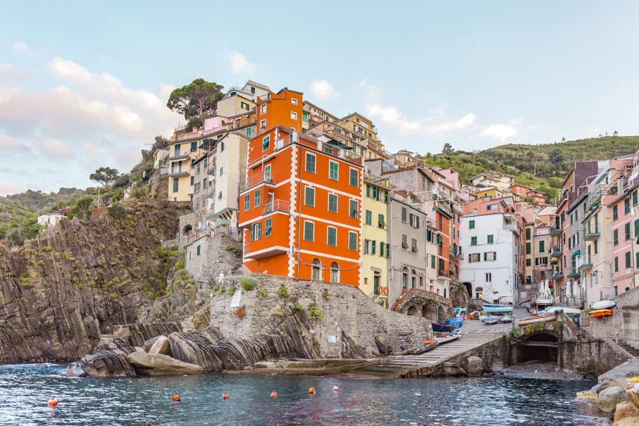 Riomaggiore city view: colorful buildings with turquoise water in front