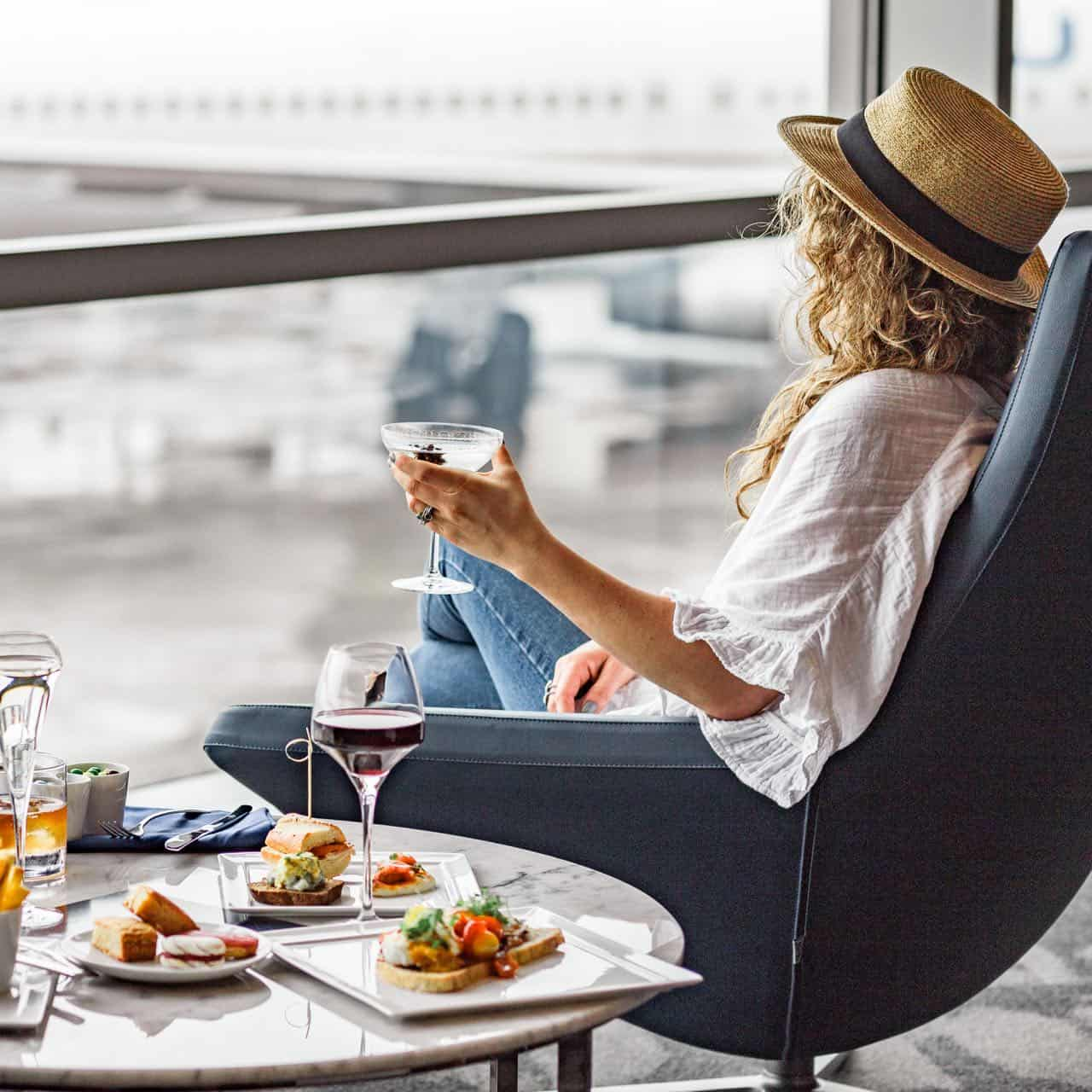 lady enjoying wine and food before a flight