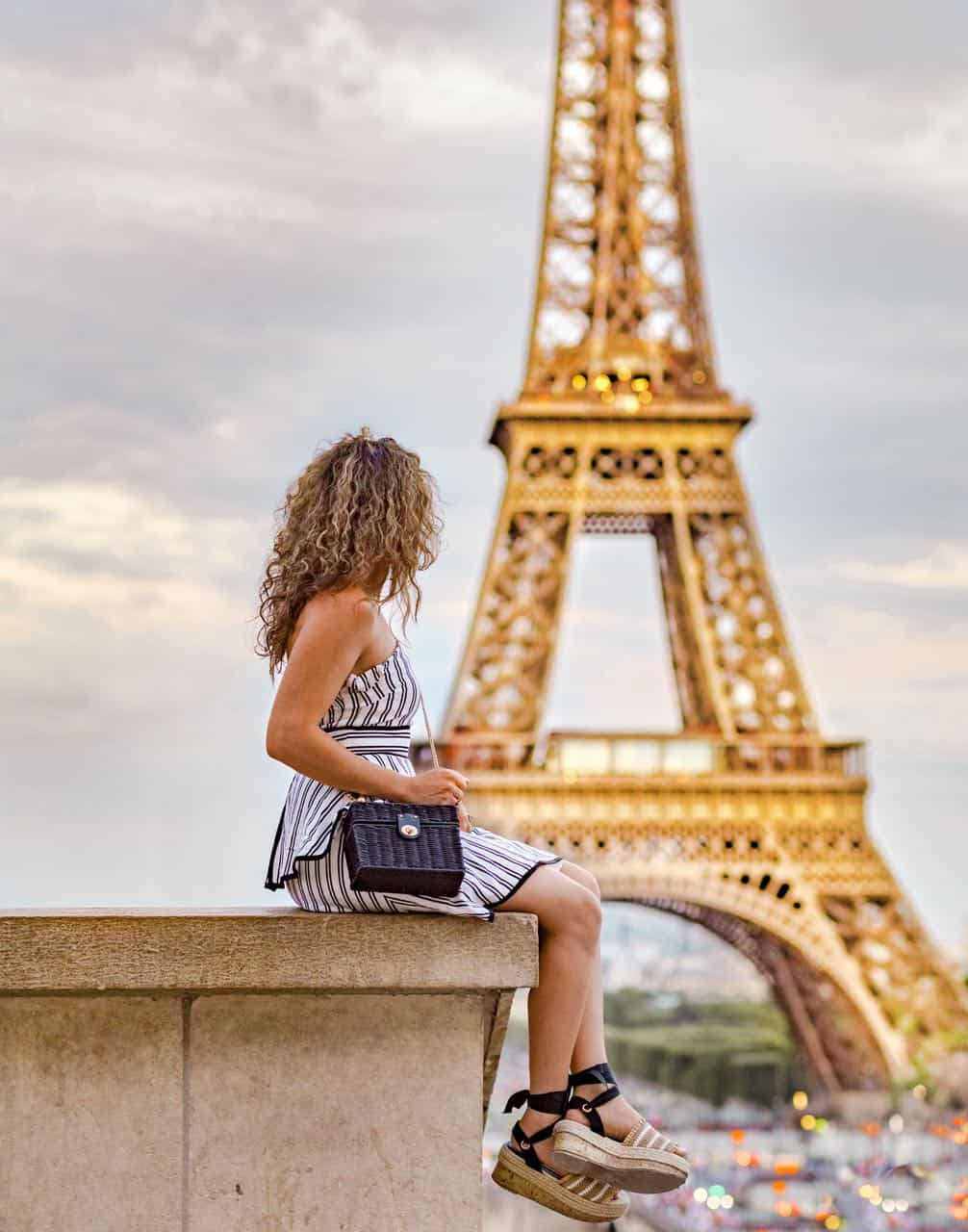girl in dress sitting on legs with Eiffel Tower in the background