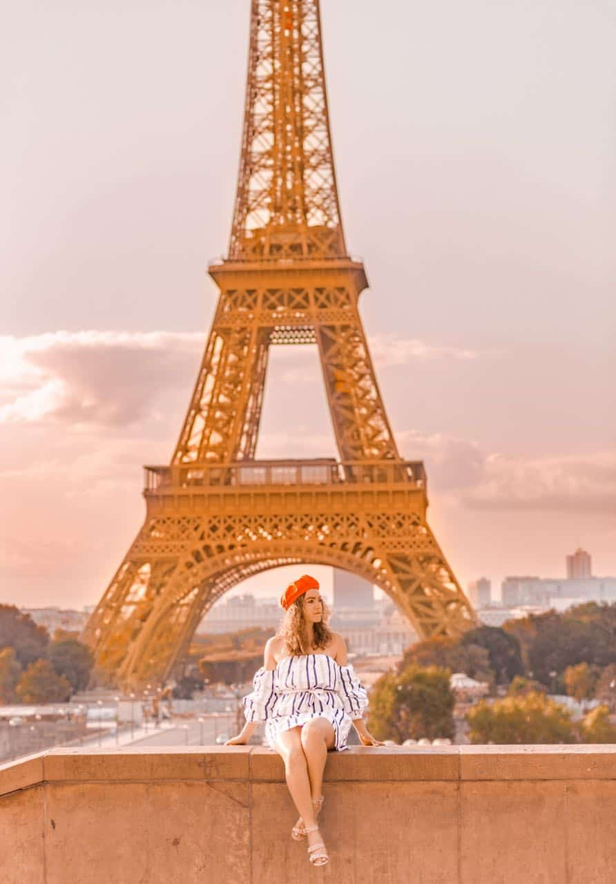 girl in beret and dress in front of Eiffel Tower