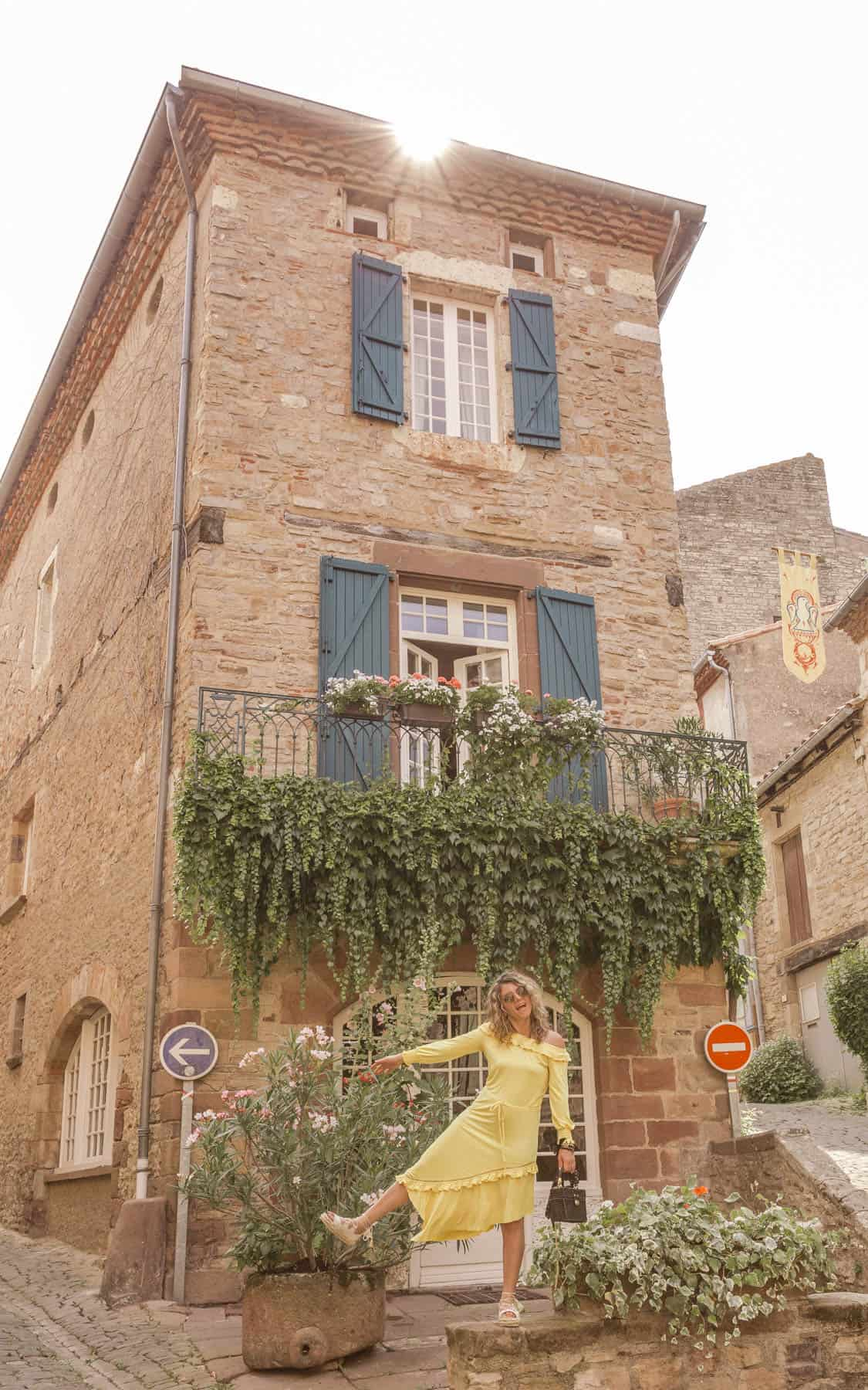 girl in yellow dress posed in front of an old French building with ivy