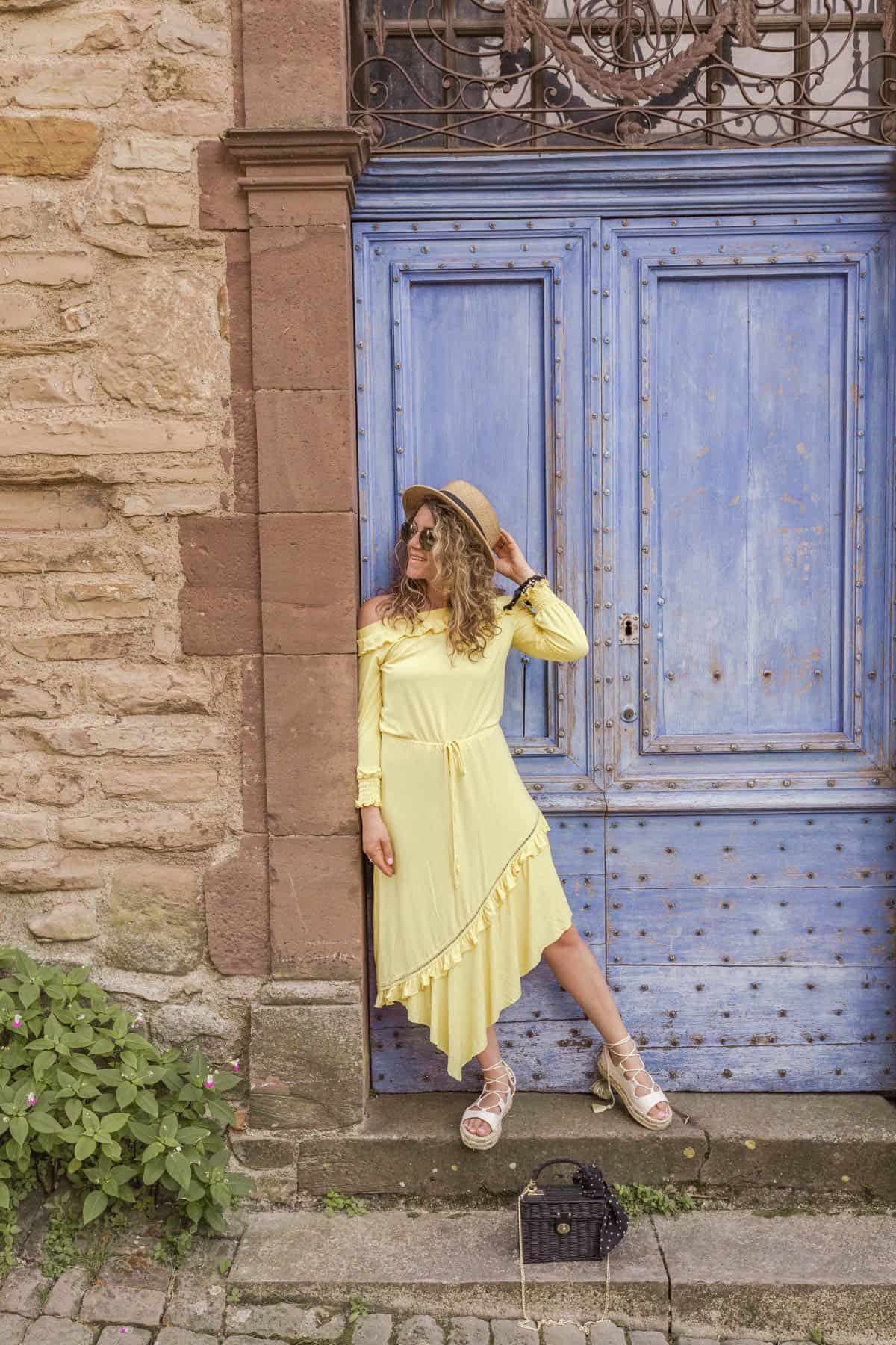 girl in yellow dress posed in front of an old blue door