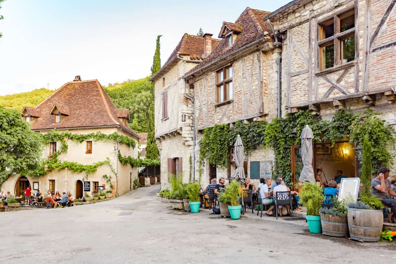scene of people sitting at a cafe in the square of an old French village