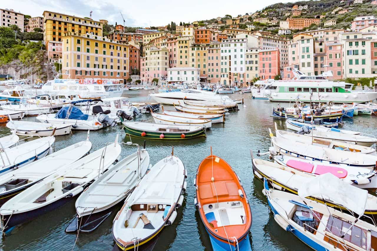 boats in a harbour with colorful buildings in the background; the town of Camogli in Italy